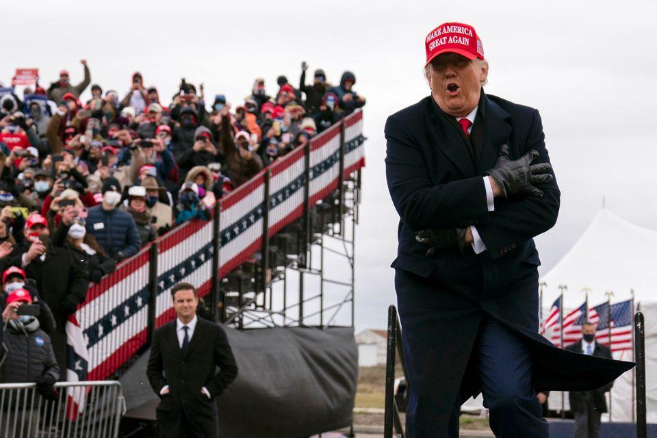 바람이 많이 불고 쌀쌀한 날씨 속에서 유세에 나선 트럼프 대통령이 춥다는 제스처를 취하고 있다. 워싱턴, 미시간주. 2020년