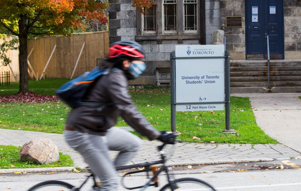 A woman wearing a face mask rides a bicycle past the Students' Union building at the University of Toronto...