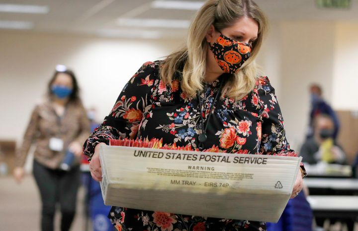 An election worker carries mail-in ballots to be processed by election workers in Salt Lake City on Oct. 29, 2020.