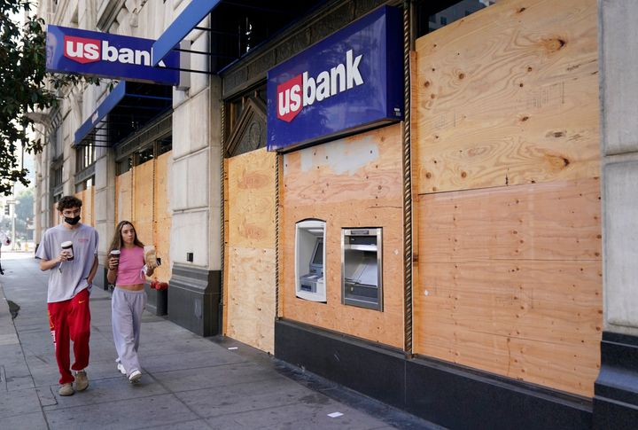 Pedestrians walk past an ATM at a boarded up US Bank branch, Monday, November 2, 2020, in downtown Los Angeles.
