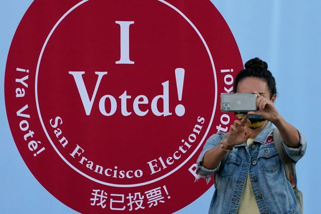 A woman takes a photo in front of an I Voted sign at a San Francisco Department of Elections voting center...