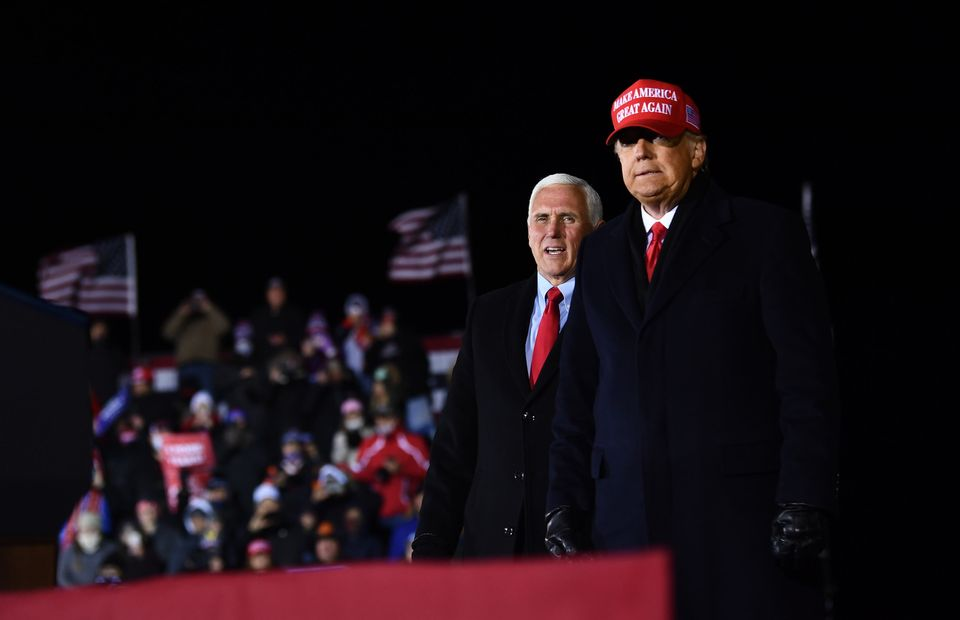 US President Donald Trump stands on stage with Vice President Mike Pence at the conclusion of his final...