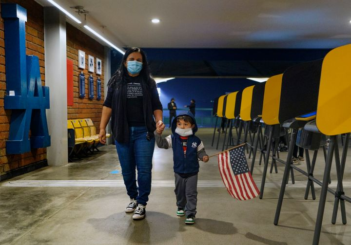 Lisa Carrera, a former Los Angeles Unified School history teacher from La Puente, Calif., holds the hand of her grandson Mave