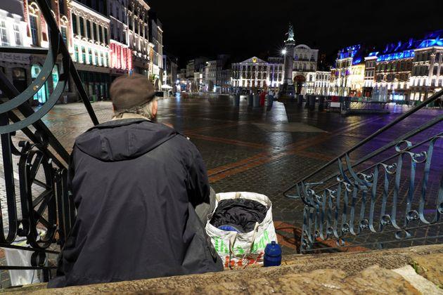 Un sans-abri est assis sur les marches du théâtre de la grande place déserte de Lille...