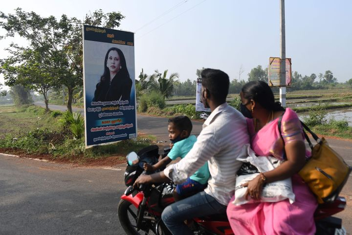 A family rides past a poster of Democratic vice presidential candidate, Kamala Harris, at her ancestral village of Thulasendr