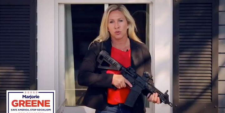 Republican Marjorie Taylor Greene, a QAnon adherent, poses with a gun in a campaign ad.