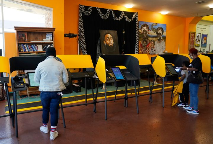 Voters work on their ballots at a polling station at the Hot and Cool Cafe, Tuesday, Nov. 3, 2020, in the Leimert Park section of Los Angeles.