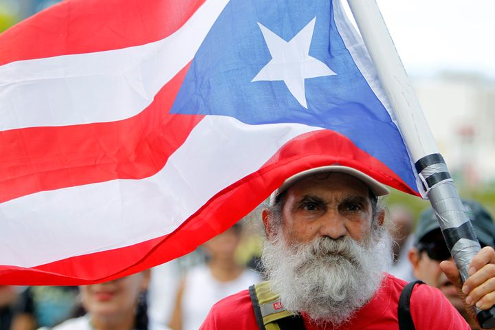 A man carries a Puerto Rican flag during a protest against the referendum for Puerto Rico political status in San Juan.
