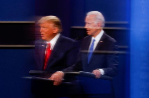 U.S. President Donald Trump and Democratic presidential nominee Joe Biden are reflected in the plexiglass...