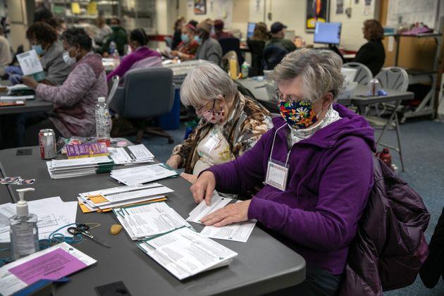 Un grupo de trabajadores cuenta los votos por correo en la ciudad de Lansing, en