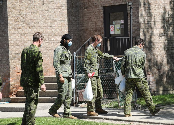 Military personnel are seen changing shifts behind the Eatonville Care Centre in Toronto, Ont. on May 26, 2020.