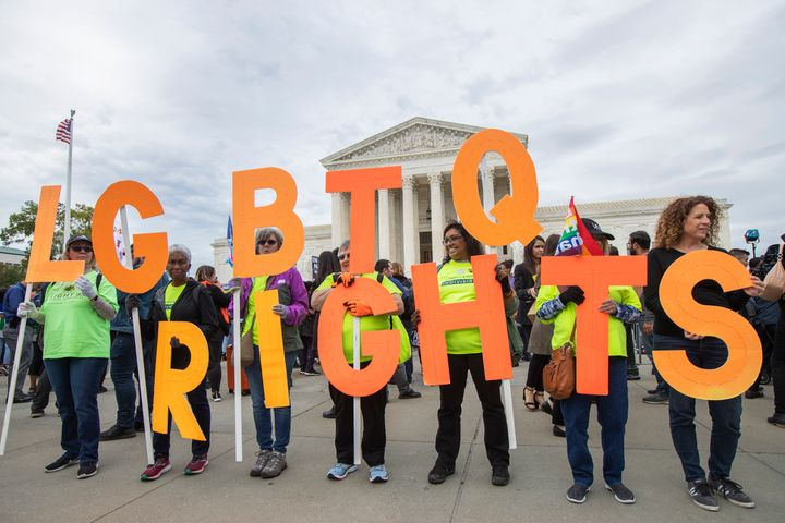 Supporters of LGBTQ rights hold placards in front of the U.S. Supreme Court, Tuesday, Oct. 8, 2019, in Washington.