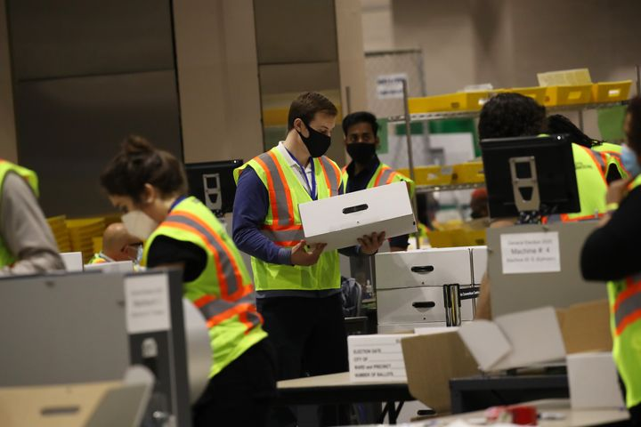 Election workers count ballots on Wednesday in Philadelphia. Despite the president's unfounded claims, voting appeared to go