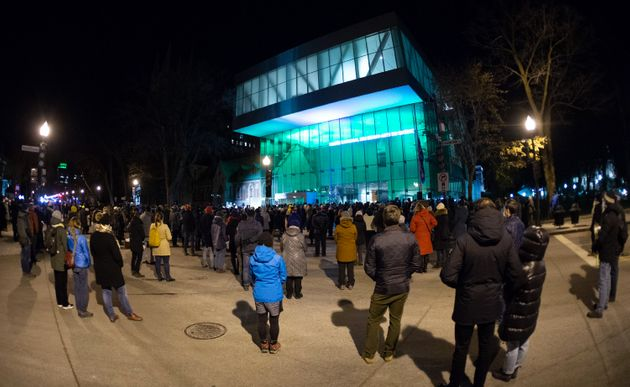 People gather at the Quebec National Museum in a vigil to honour Francois Duchesne who was stabbed to...