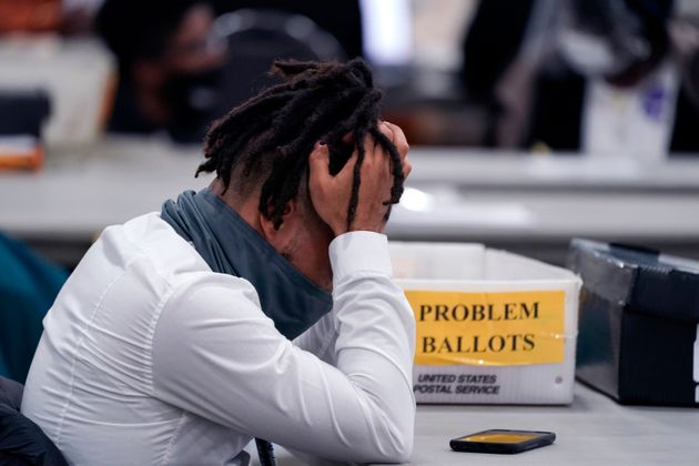 An elections worker rubs his head in the closing hours where absentee ballots were processed at the central...