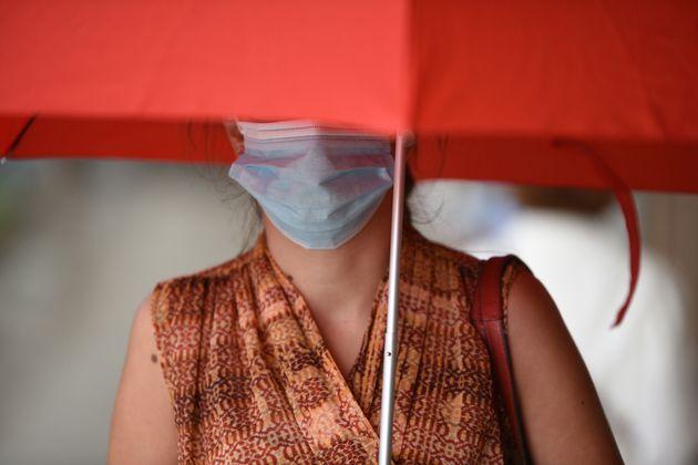 Una mujer, con un paraguas y una mascarillas