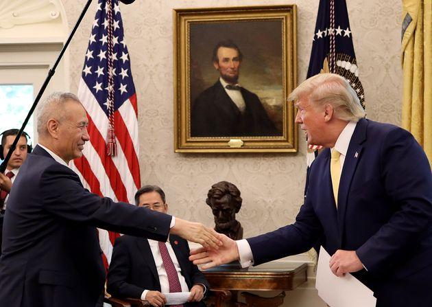 El presidente de Estados Unidos, Donald Trump, saluda al vicepresidente de China, Liu He, para anunciar...