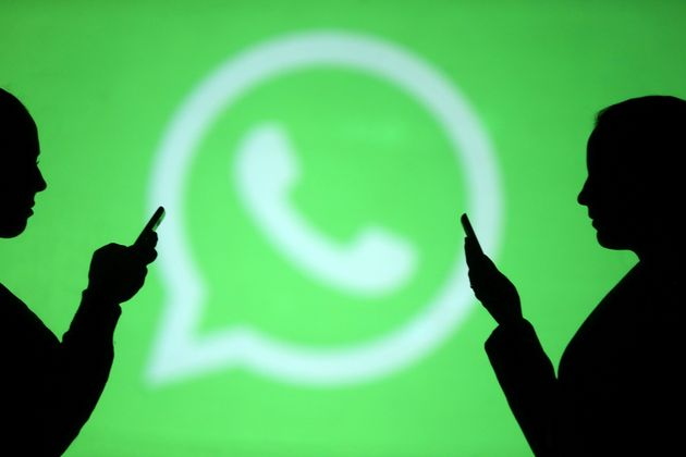 Silhouettes of mobile users are seen next to a screen projection of Whatsapp logo in this picture illustration...