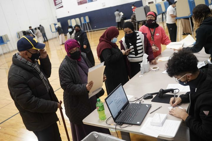 Dawleh Ahmed (second from left) and Naji Ahmed (left) wait in line to vote at Salina Elementary School on Nov. 3 in Dearborn,
