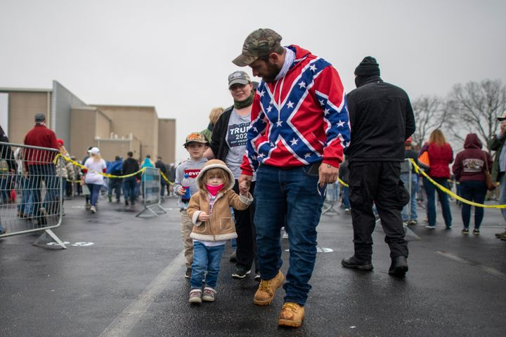 A man wearing a Confederate flag-themed sweatshirt walks with his children while queuing before President Donald Trump holds