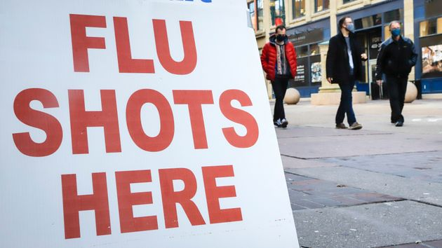 People wear masks as they pass a pharmacy offering flu shots in downtown Calgary, Alta., on Oct. 30,