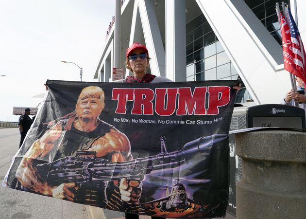 A Trump supporter holds a flag depicting the president as Rambo during a protest outside State Farm Arena...