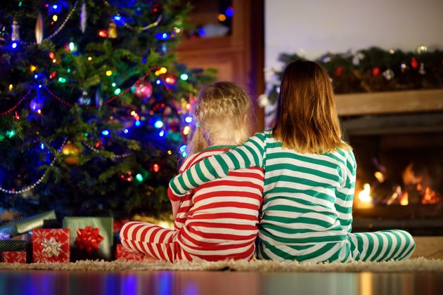 Happy little sisters wearing Christmas pajamas opening gift boxes by a fireplace in a cozy dark living...
