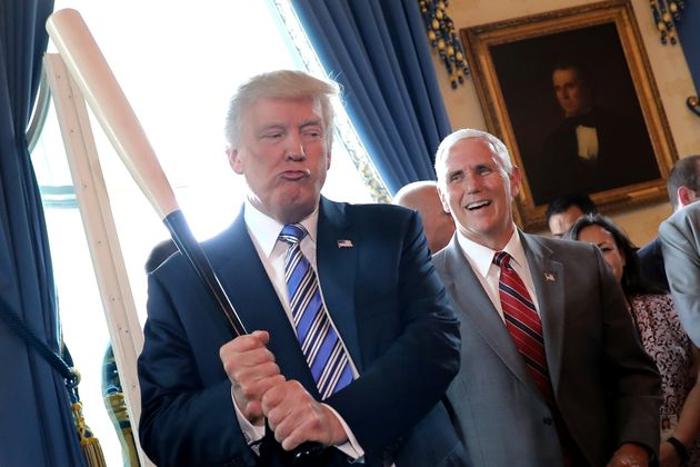 Vice President Mike Pence laughs as U.S. President Donald Trump holds a baseball bat as they attend a...