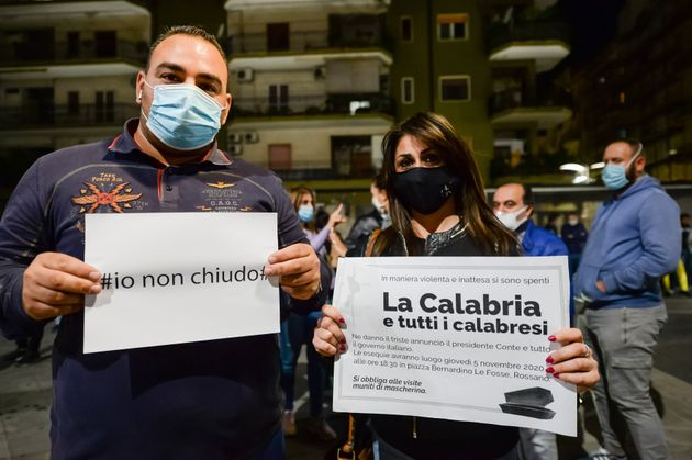 CORIGLIANO-ROSSANO, COSENZA, ITALY - 2020/11/05: Two Calabrian traders show a sign with the words