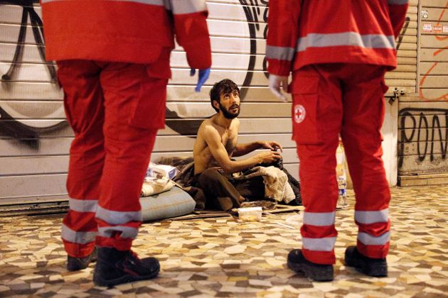 A homeless person talks to Red Cross workers in Rome, Italy, March 17, 2020. Since the coronavirus crisis,...