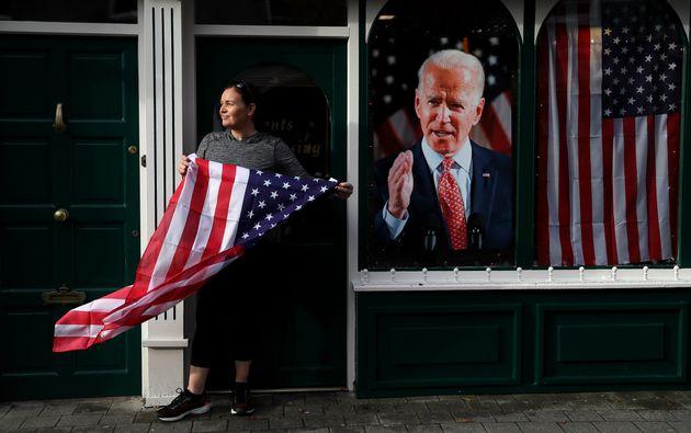 Una mujer celebra junto a una imagen de Joe Biden la victoria de este en las elecciones presidenciales...