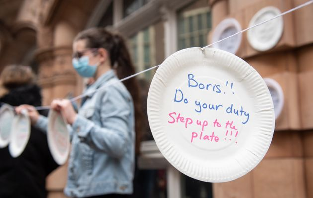 Protestors hang up paper plates carrying slogans calling for the government to extend free school meals...