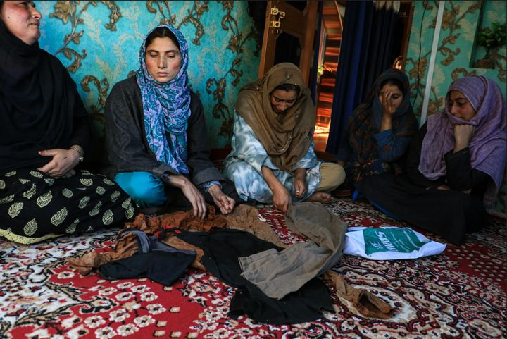 Rifleman Shakir Manzoor Waghay's family members cry while showing his clothes that were found after he was kidnapped.