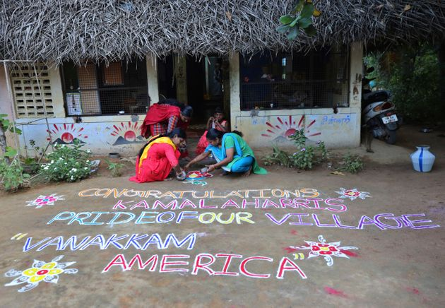 Indian women prepare a Kolam, a traditional art work using colored powder, congratulating Harris in the...
