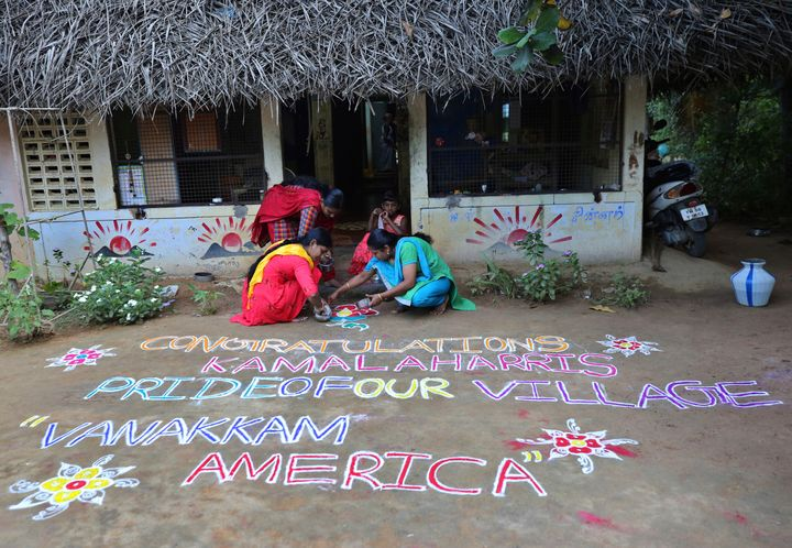 Indian women prepare a Kolam, a traditional art work using colored powder, congratulating Harris in the hometown of Harris' m