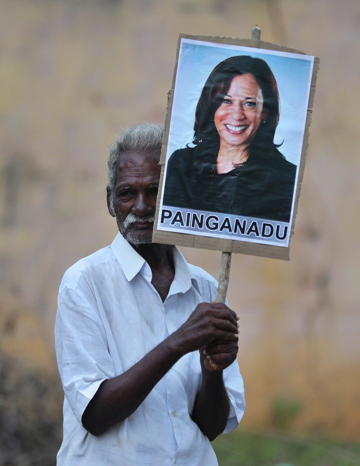An elderly villager holds a placard of the U.S. vice president-elect during celebrations for her victory in Painganadu, a nei