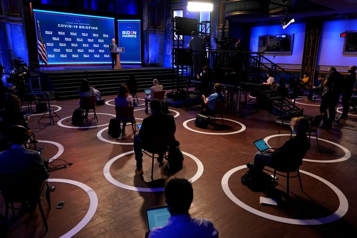 In this Sept. 1, 2020, file photo journalists sit in socially-distant circles as Democratic presidential candidate former Vic
