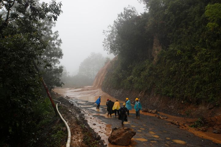 Workers walk around a road blocked by a landslide in San Cristobal Verapaz, Guatemala, on Saturday following Hurricane Eta. A