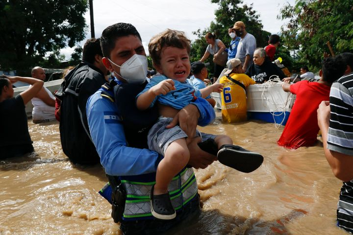 A toddler is carried over a flooded street in the aftermath of Hurricane Eta in Jerusalen, Honduras, on Thursday. The storm h