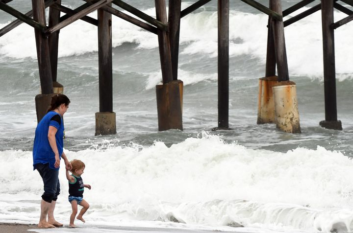 A mother lets her child play in the surf as heavy waves from Tropical Storm Eta come on the shore near the Cocoa Beach Pier i
