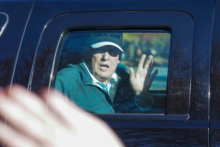President Donald Trump waves to supporters as he departs after playing golf at the Trump National Golf Club in Sterling Va., on Nov. 8, 2020.