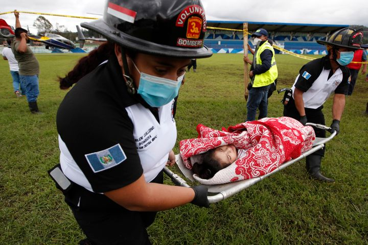 First responders rescue a girl who was buried by a massive, rain-fueled landslide Saturday in the aftermath of Tropical Storm