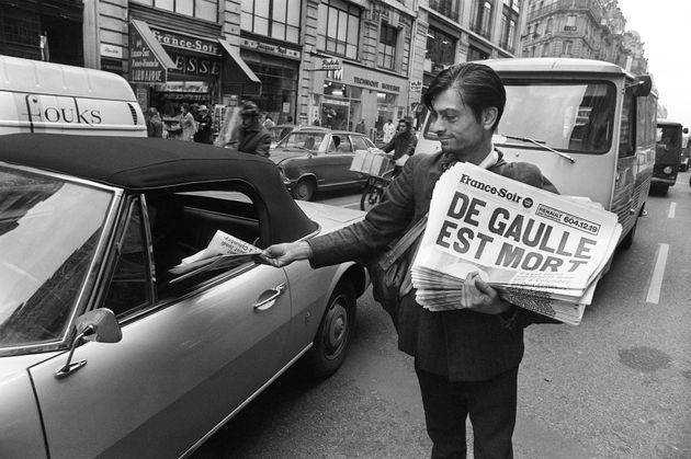Un vendeur de rue propose à un automobiliste le journal France-Soir annonçant la mort du...