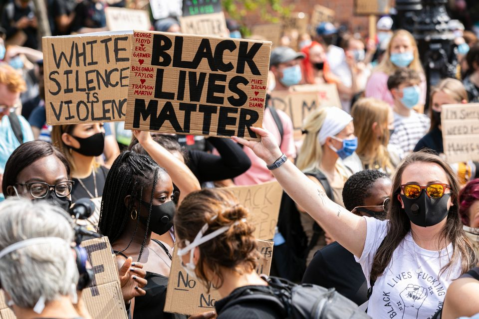 Protesters hold placards as they march during a demonstration in Millennium