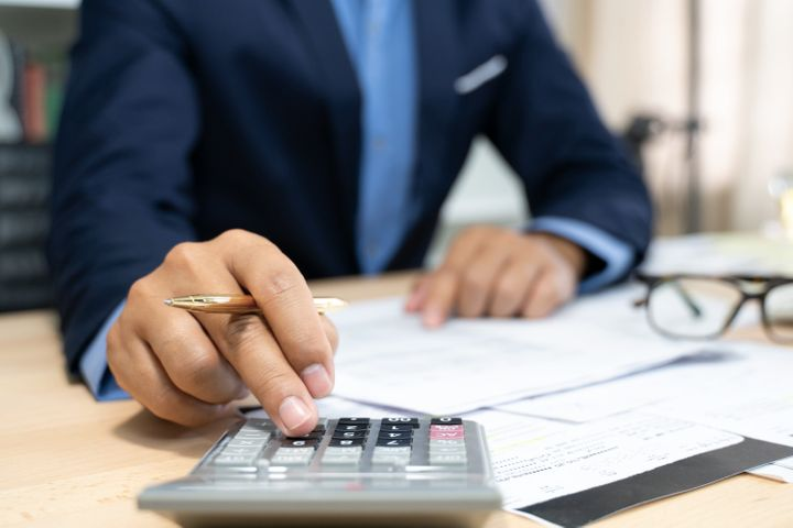 A financial expert calculates a mortgage down payment in this undated stock photo.Besides the financial savings, a larger down payment will also increase your overall affordability.