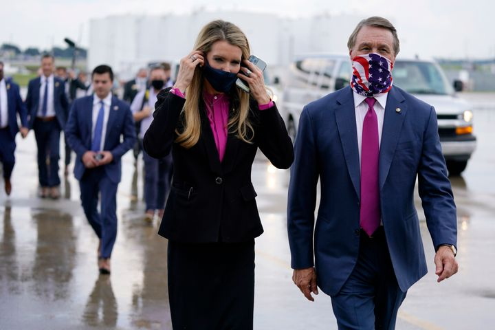 Sen. Kelly Loeffler (R-Ga.) walks with Sen. David Perdue (R-Ga.) in July in Atlanta. Both will be competing to hold on to the