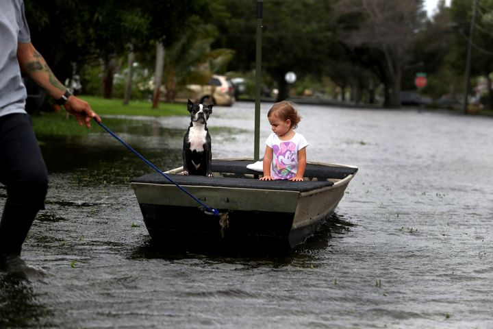 Lemay Acosta pulls his daughter Layla, 2, and dog Buster on a boat as they tour his flooded neighborhood in Plantation, Fla.,