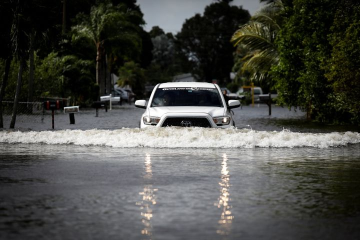A commuter drives in floodwaters caused by Tropical Storm Eta in Davie, Florida.