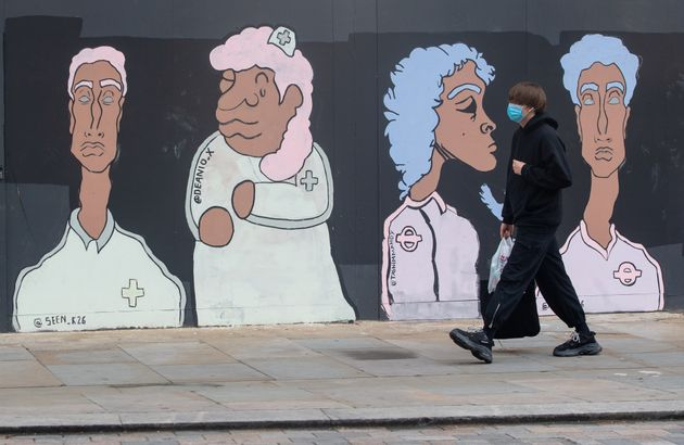 A man wearing a protective face mask passes a mural showing Black and Asian medical and transport workers, in Waterloo