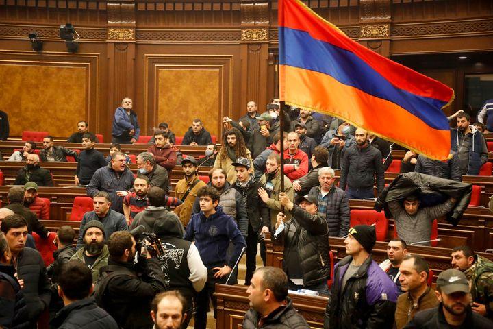 Manifestantes con una bandera nacional armenia protesta contra un acuerdo para detener los combates en la región de Nagorno-Karabaj,